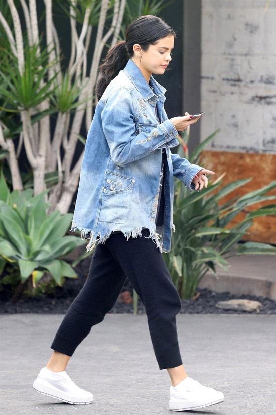 Девушка в черных штанах, джинсовая куртка оверсайз и белые кеды