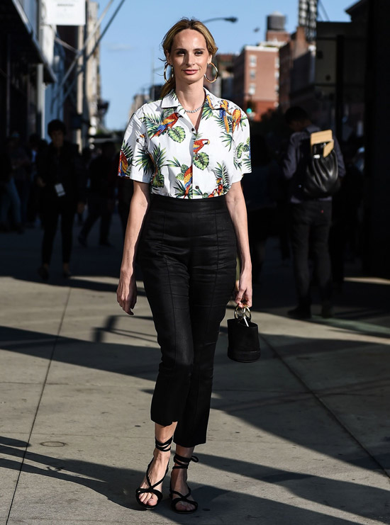 Девушка в черных укороченных брюках, белая рубашка с тропическим принтом и сандалии