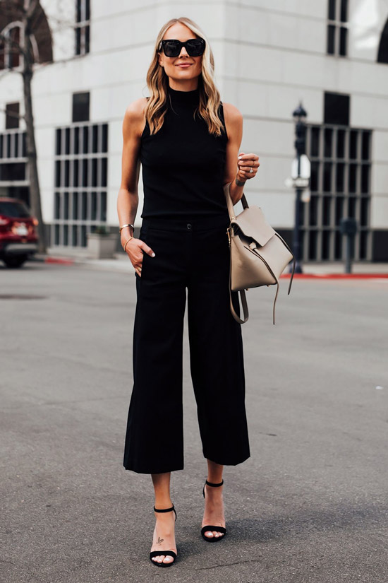 Девушка в черных укороченных брюках, топ и босоножки