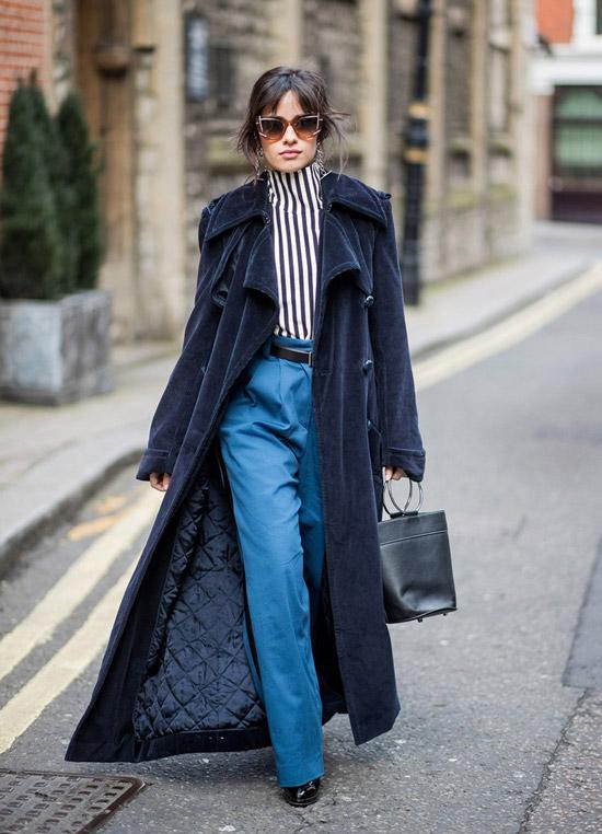 Девушка в длинном пальто, синие брюаи и блузка в полоску