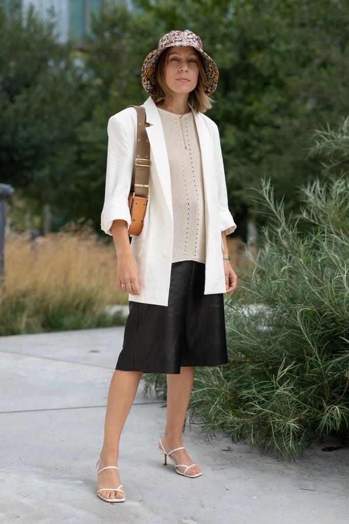 Девушка в длинных черных шортах, белый блейзер оверсайз, белые босоножки