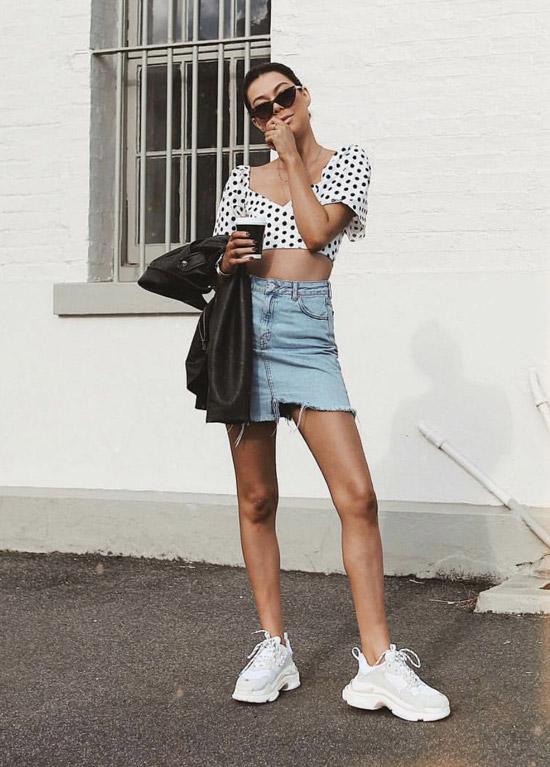 Девушка в джинсовой мини юбке, кроп топ и белые кроссовки
