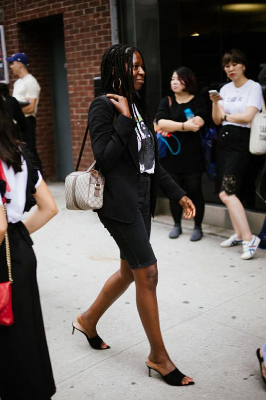 Девушка в джинсовых шортах выше колена, блейзер и футболка с принтом