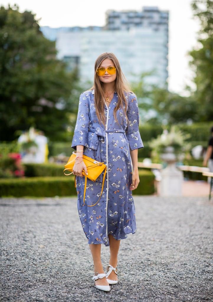 Девушка в голубом платье с поясом, желтая сумка и белые туфли