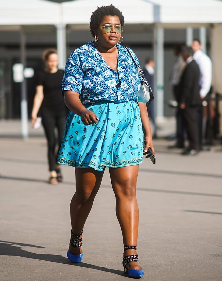 Девушка в голубой мини юбке, рубашка с цветочным принтом и синие туфли