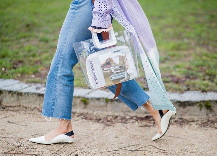 Девушка в голубых рванных джинсах, белые туфли и прозрачная сумка