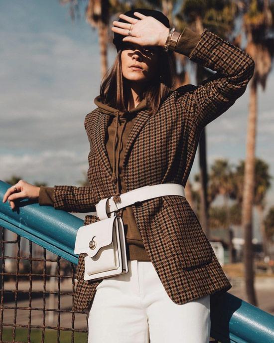 Девушка в коричневом пиджаке в клетку, худи и белые джинсы