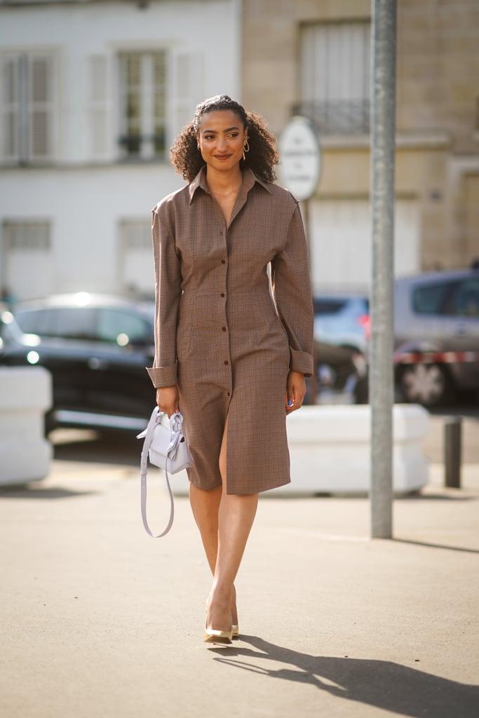 Девушка в коричневом платье по колено с длинными рукавами, золотые туфли и белая сумка