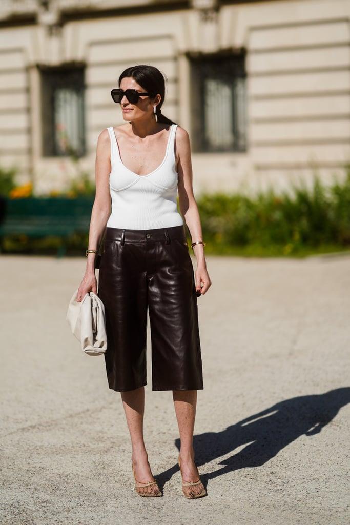 Девушка в кожаных шортах ниже колен, белый топ и бежевые туфли