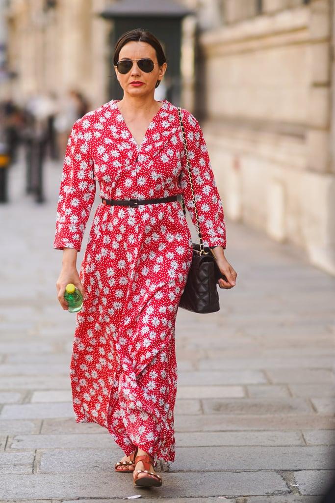 Девушка в красном платье с белым цветочным принтом и тонким поясом, коричевые сандалии и сумка