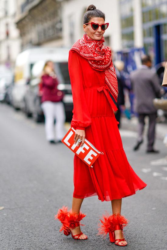 Девушка в красном платье с длинными рукавами, красные туфли на каблуке и клатч