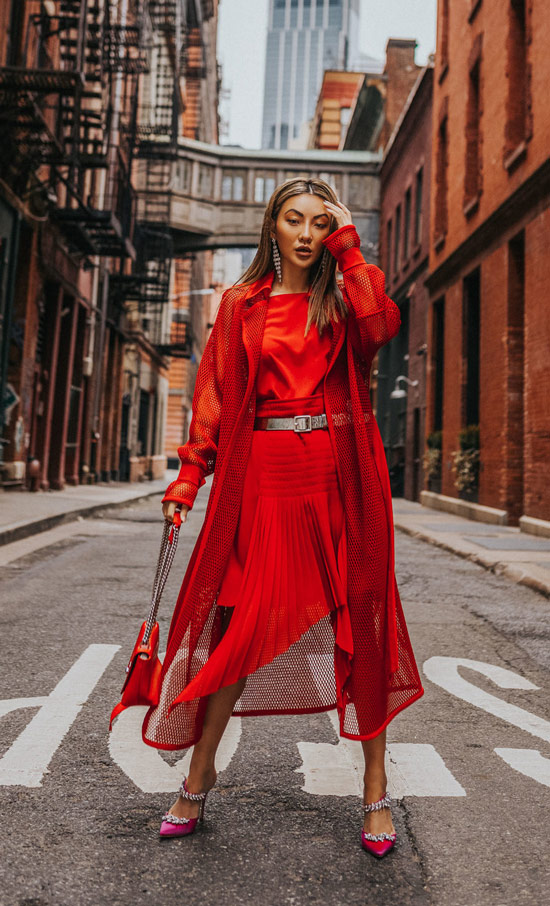 Девушка в красном платье с ремнем, розовые туфли с украшениями и красный клатч