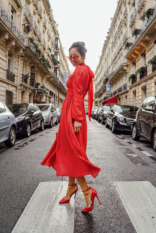 Девушка в красном платье в горох, красные туфли и солнцезащитные очки