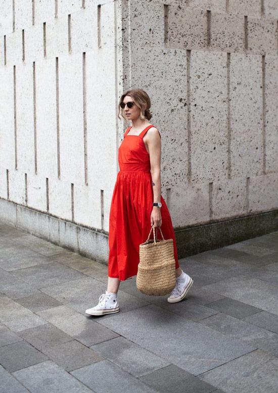Девушка в красном сарафане, белые кеды и соломенная сумка