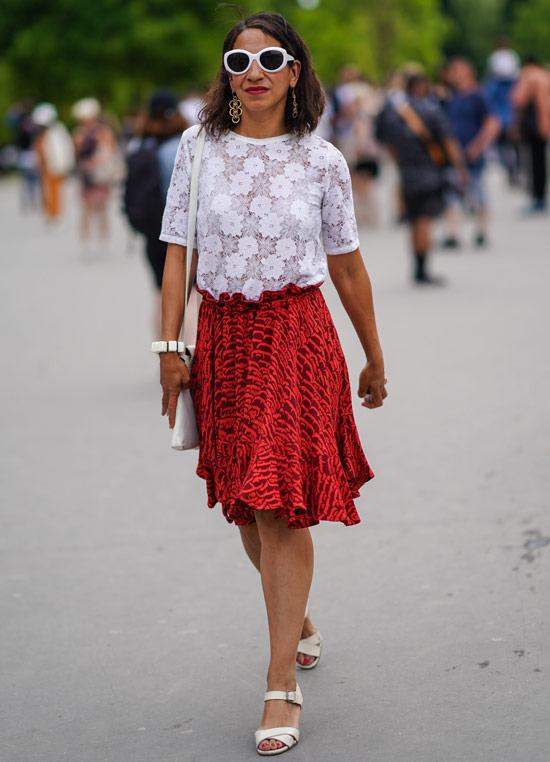 Девушка в красной юбке по колено, белая кружевная футболка и босоножки