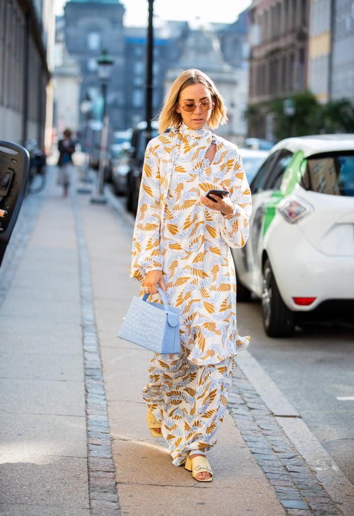 Девушка в легком романтичном платье с принтом, желтые босоножки и голубая сумка