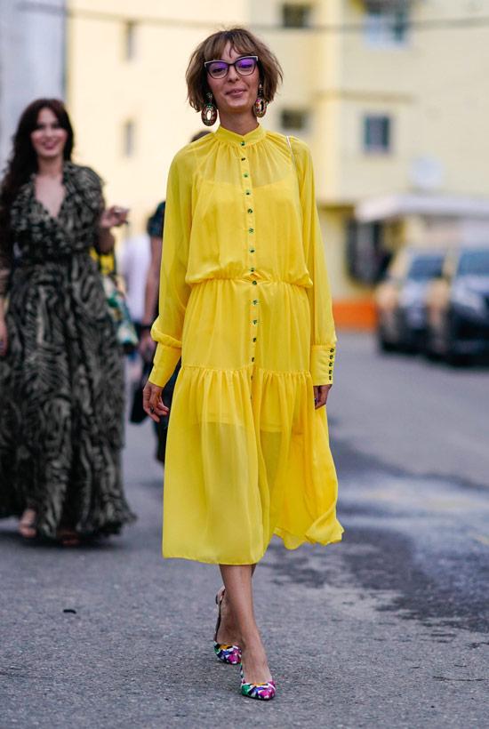 Девушка в легком желтом платье миди и разноцветных туфлях