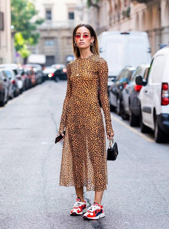 Девушка в леопардовом платье с длинными рукавами и кроссовках с яркими вставками