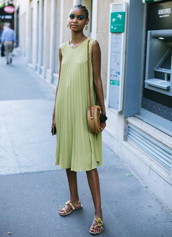 Девушка в мятно-зеленом плиссированном платье, соломенная сумка и сандалии
