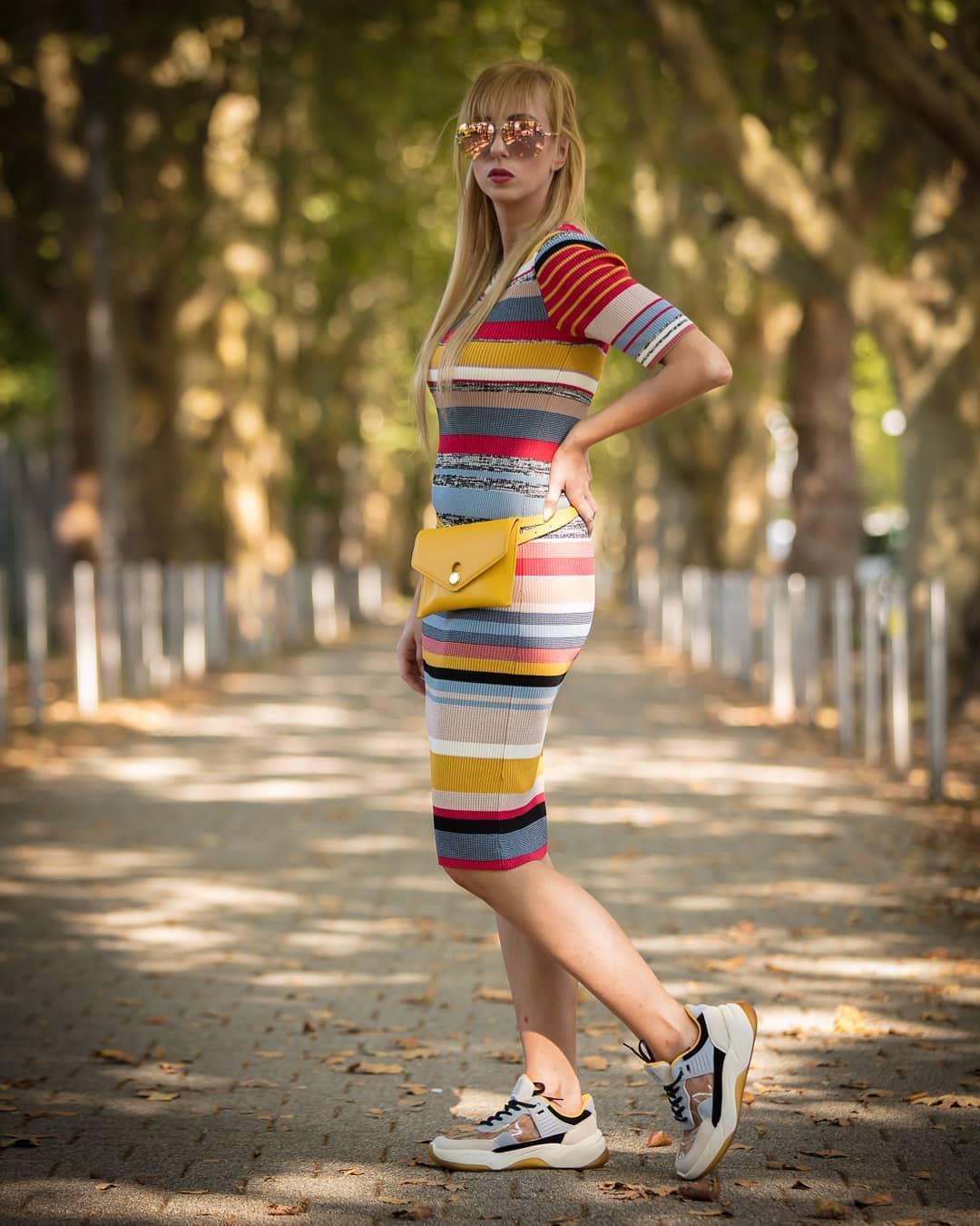 Девушка в облегающем платье в полоску и серых кроссовках