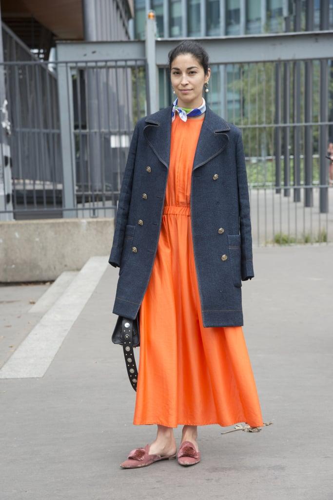 Девушка в оранжевом длинном платье, черное пальто и сандалии