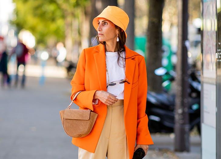 Девушка в оранжевом пиджаке, белая футболка и панама