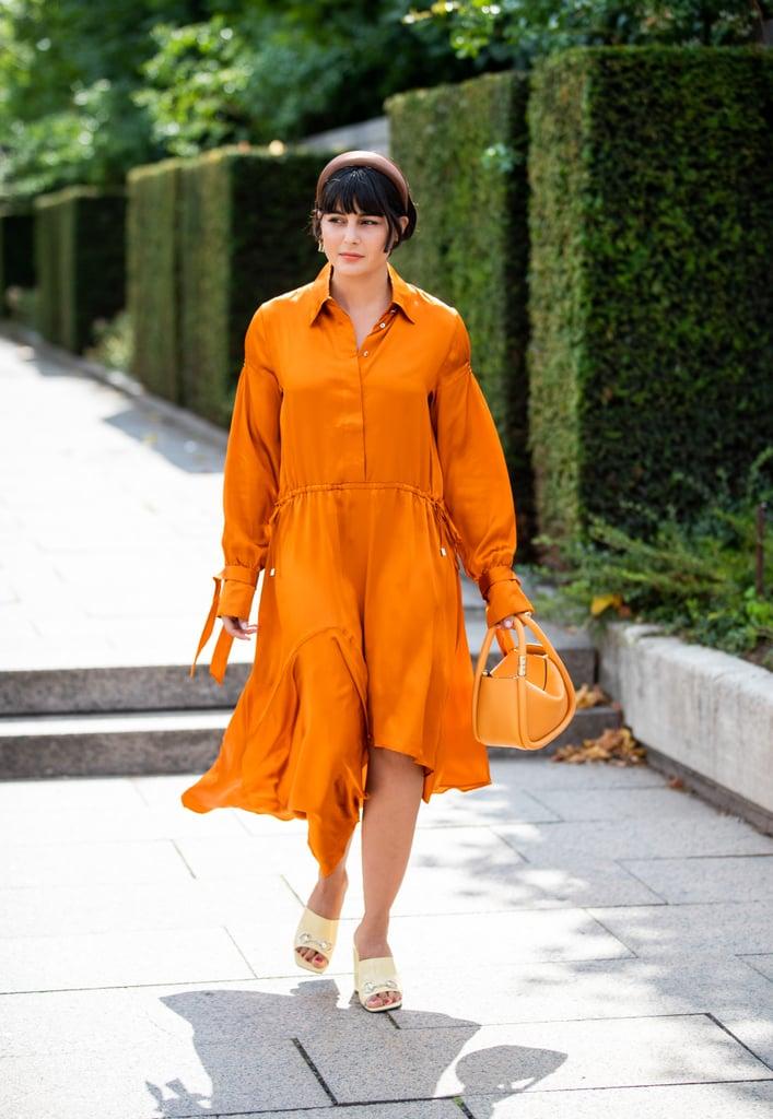 Девушка в оранжевом платье и светлые туфли