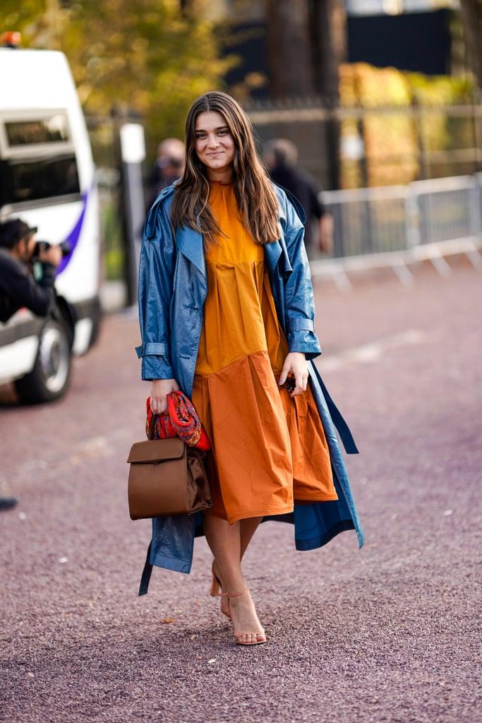 Девушка в оранжевом платье свободного кроя, синий плащ и коричневая сумка