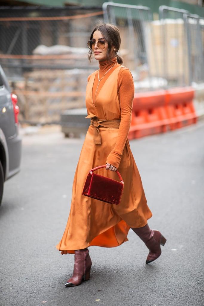 Девушка в оранжевом шелковом платье, водолазка и бордовые сапоги