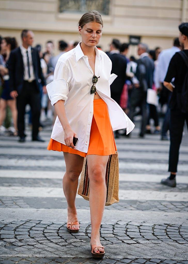 Девушка в оранжевой юбке мини, белая рубашка оверсайз и сандалии
