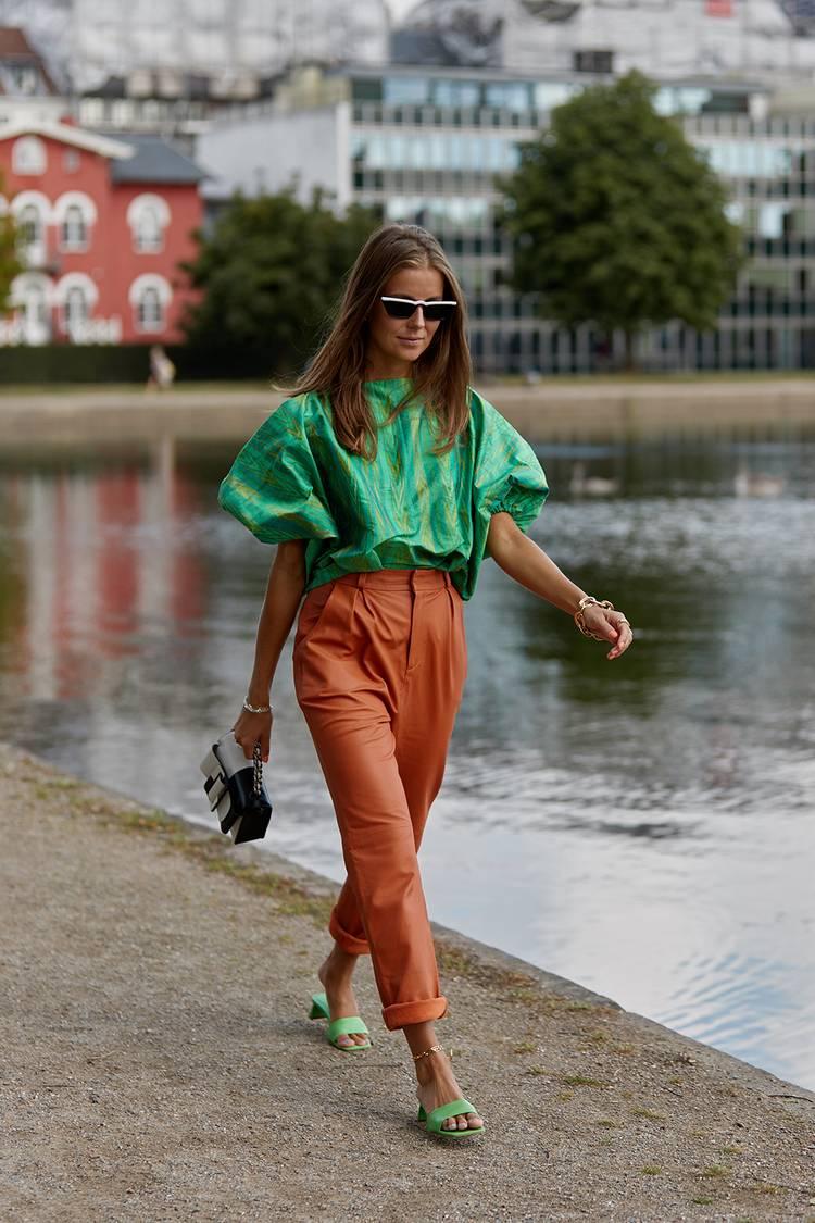 Девушка в оранжевых брюках, зеленая блузка и сандалии