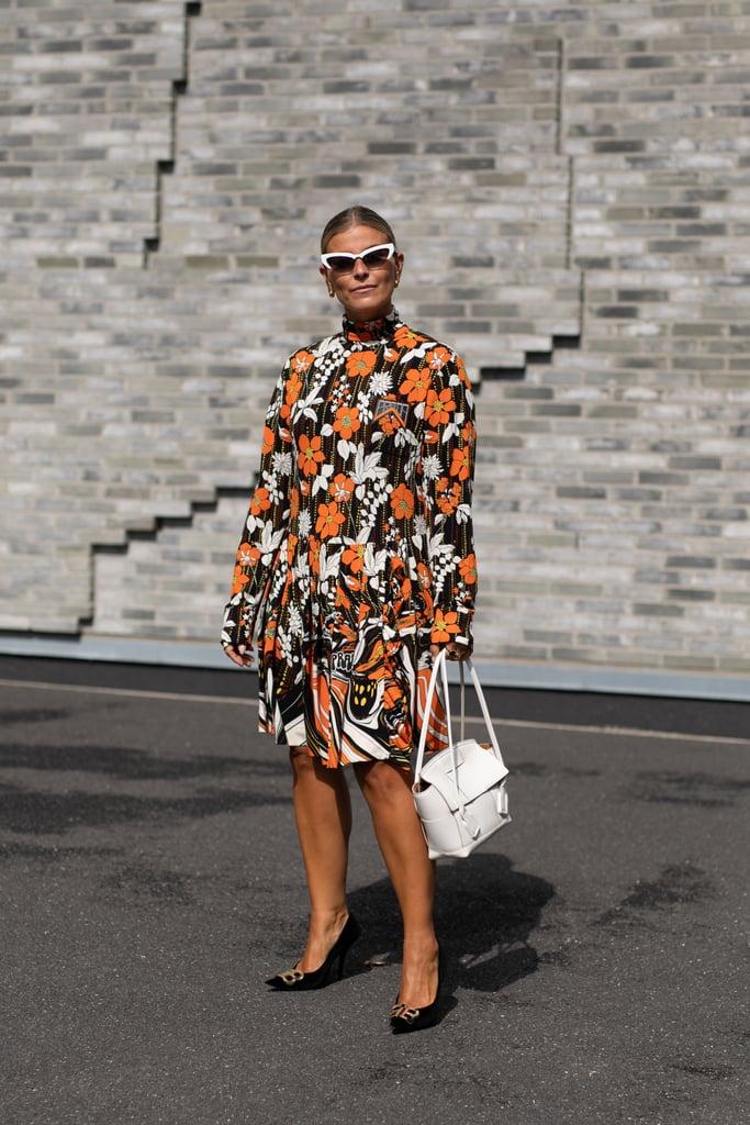 Девушка в осеннем платье по колено с цветочным принтом, черные туфли и белая сумка
