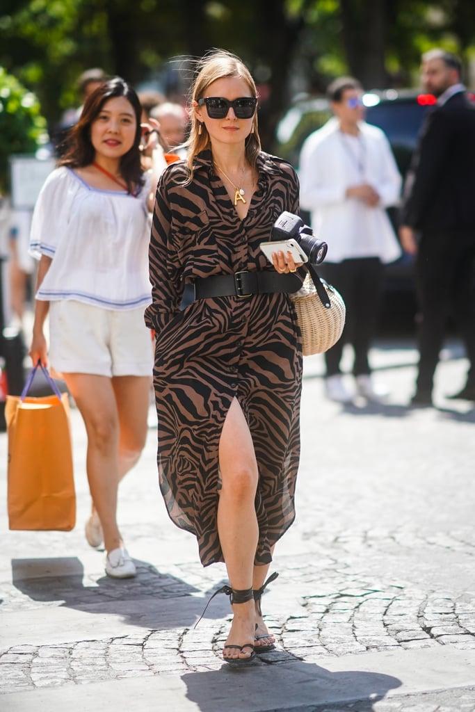 Девушка в осеннем платье с тигрорым принтом с ремнем, черные сандалии и соломенна сумка