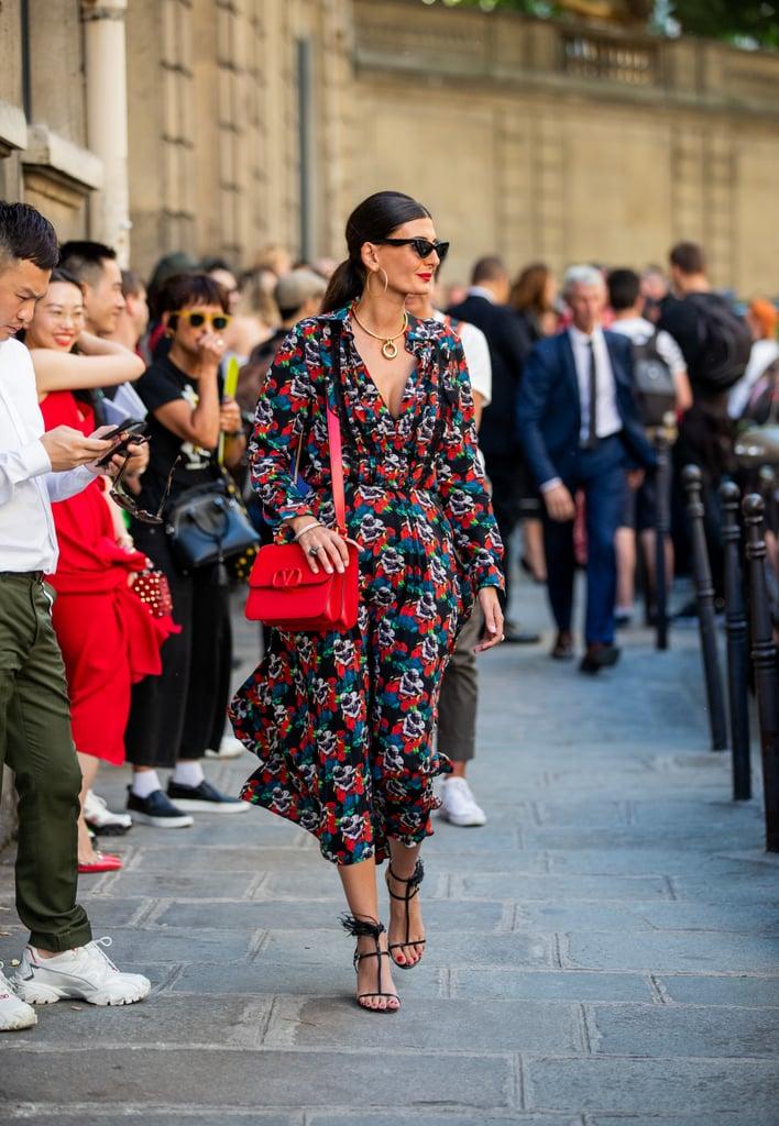 Девушка в пестром платье миди с цветочным принтом, черные босоножки и красная сумка