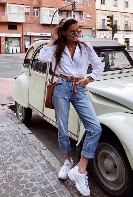 Девушка в подвернутых джинсах, белая рубашка и кроссовки
