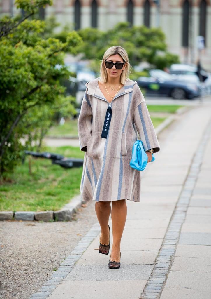 Девушка в просторном платье в полоску, черные туфли и голубая сумка