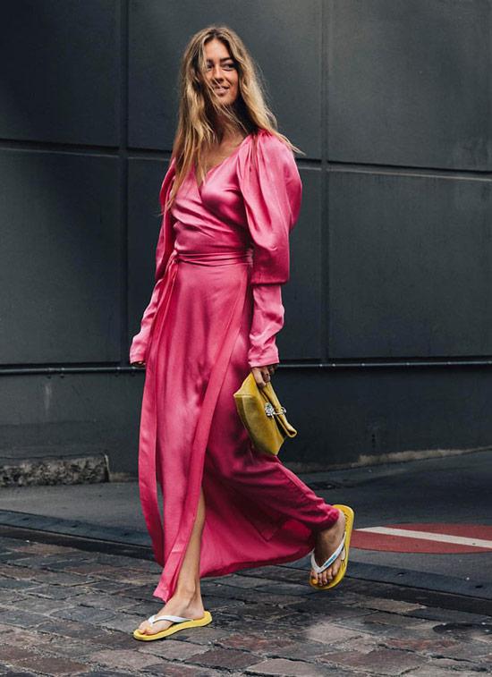 Девушка в розовом атласном платье с длинными рукавами, желтый клатч и шлепки