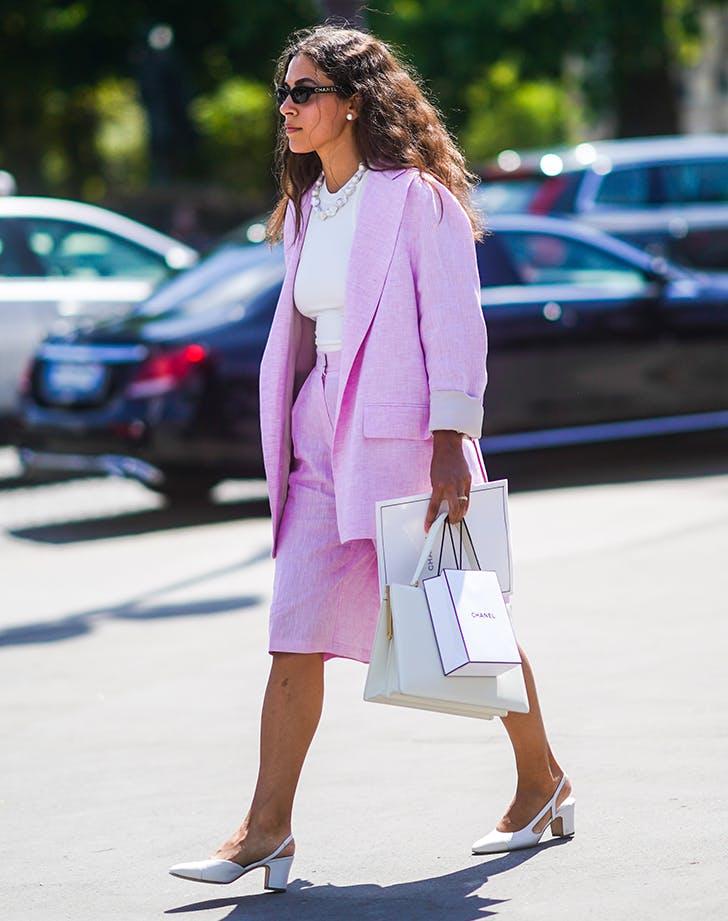 Девушка в розовом костюме с шортами бермудами, белая футболка и туфли с отрытой пяткой