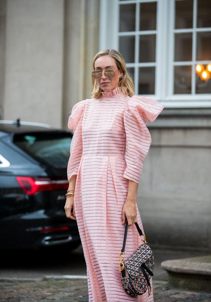 Девушка в розовом платье с рюшами и серая сумка