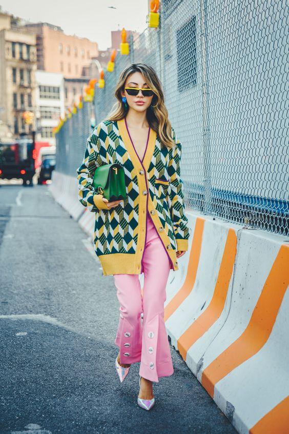 Девушка в розовых брюках клеш, желто-зеленый кардиган в ромбик и зеленая сумка