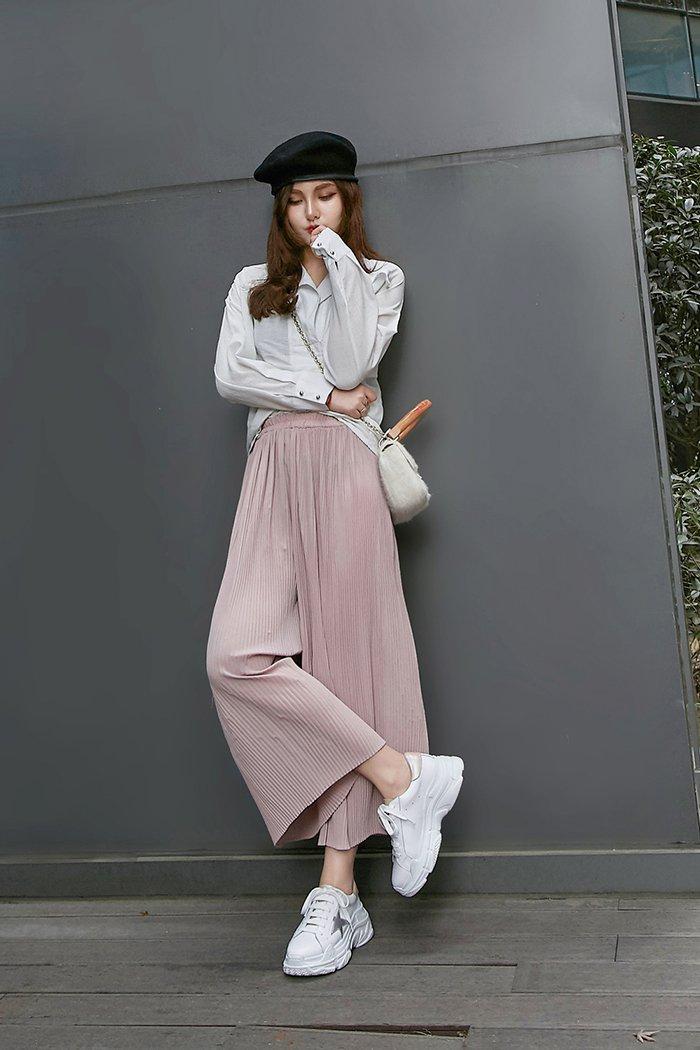 Девушка в розовых широких брюках, белая рубашка и кроссовки