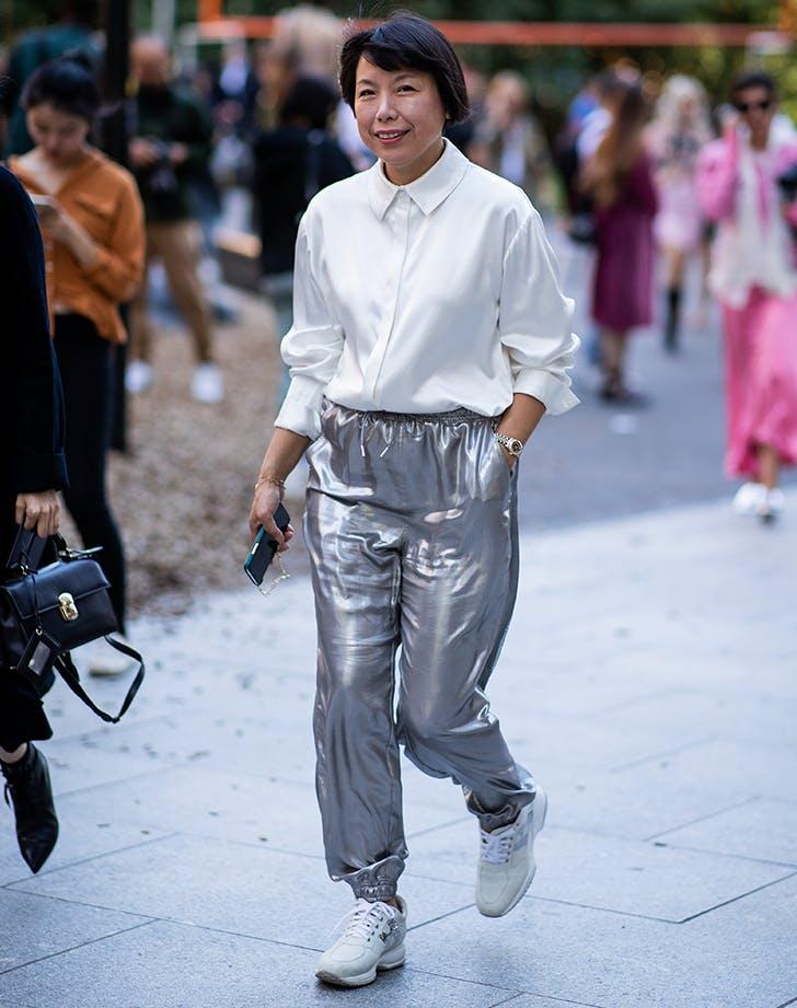Девушка в серебристых спортивных штанах, белая блузка и кроссовки