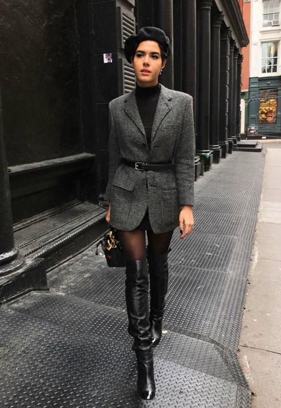 Девушка в сером блейзере с ремнем, черные ботфорты и берет