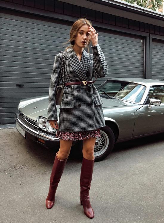 Девушка в сером блейзере с ремнем, мини юбка и бордовые сапоги