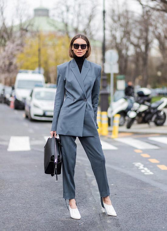 Девушка в сером деловом костюме с брюками, черная водолазка и белые туфли