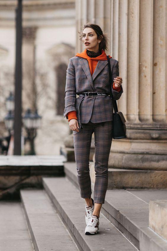Девушка в сером костюме в клетку, оранжевая толстовка и кроссовки