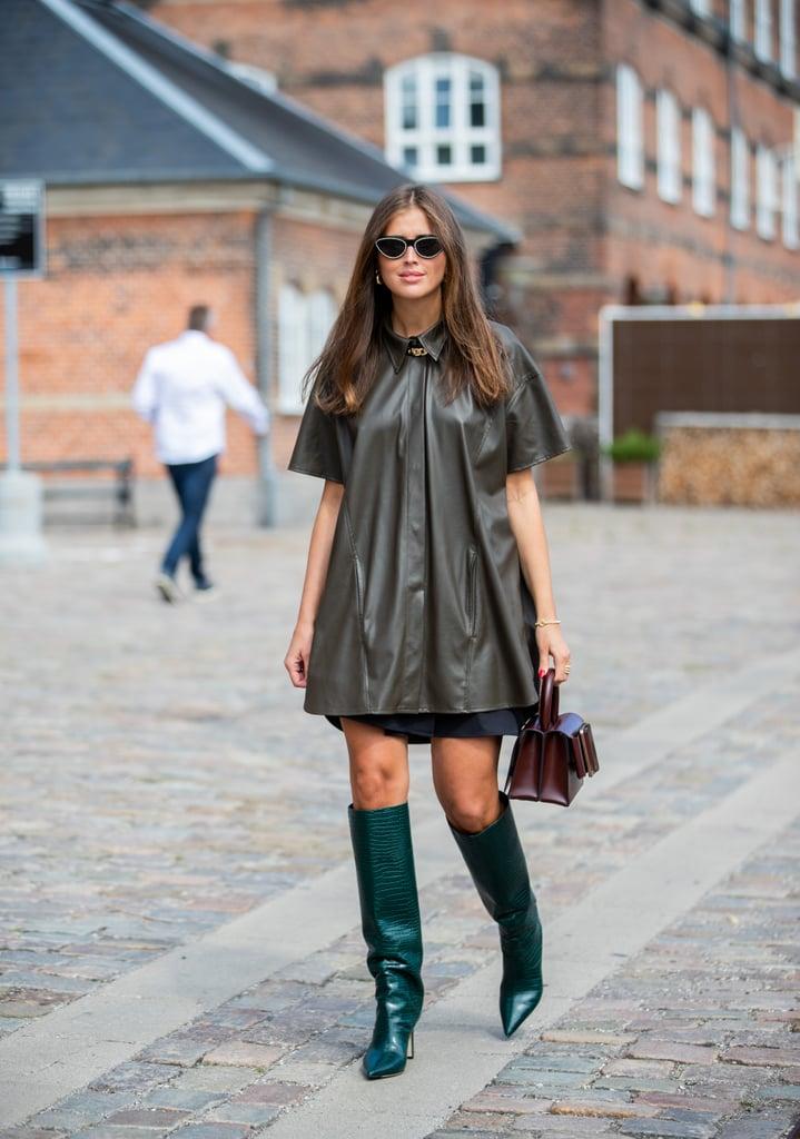 Девушка в сером мини платье, зеленые сапоги на шпильке