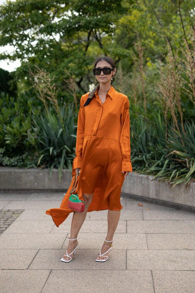 Девушка в шелковом оранжевом платье миди и белых босоножках с ремешками