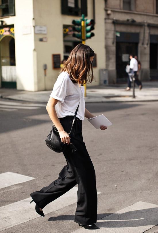 Девушка в широких брюках, белая футболка и черные туфли