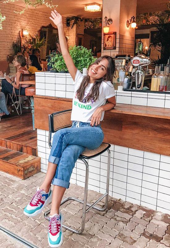 Девушка в синих джинсах, белая футболка и яркие кроссовки